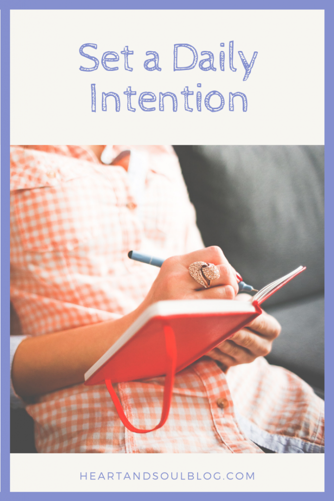 "a woman with a sparkly ring writes in a red journal with the title ""Set a Daily Intention"""