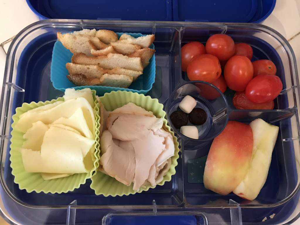 Example of school lunches with turkey, cheese, bagel chips, grape tomatoes, apple slices, and chocolate chips/marshmallows.