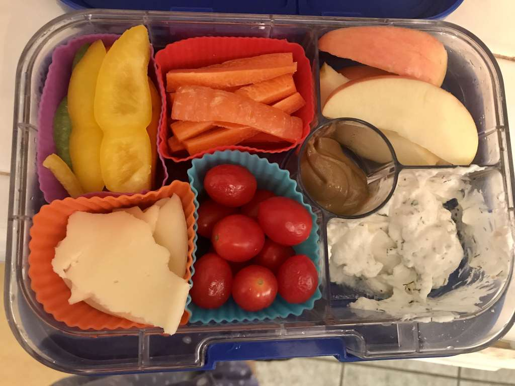 Example of school lunches with pepper slices, carrot sticks, provolone cheese, cherry tomatoes, apple slices, homemade ranch dip (Greek yogurt + dried herbs), and sunflower seed butter.