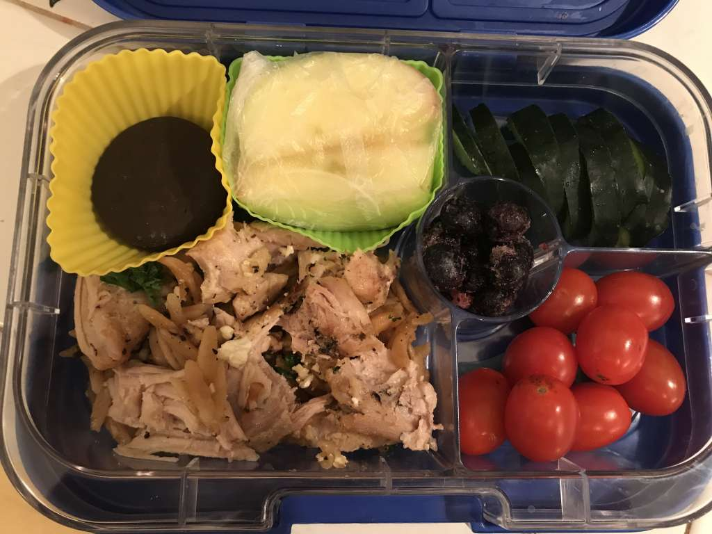 Example of school lunches with leftover chicken and orzo, apple slices, grape tomatoes, cucumber slices, frozen blueberries, and a chocolate mint cookie.