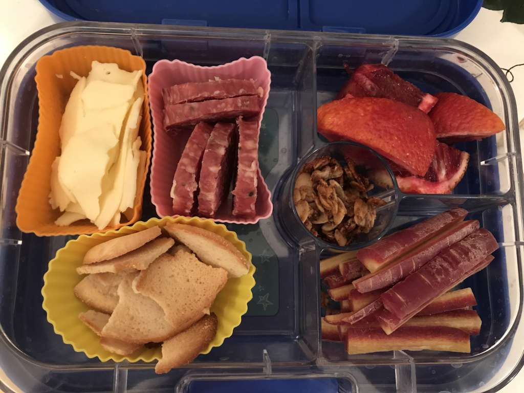 Child's bento box with provolone cheese, sliced salami, bagel chips, sliced blood orange, purple carrot sticks, and homemade nut-free granola.