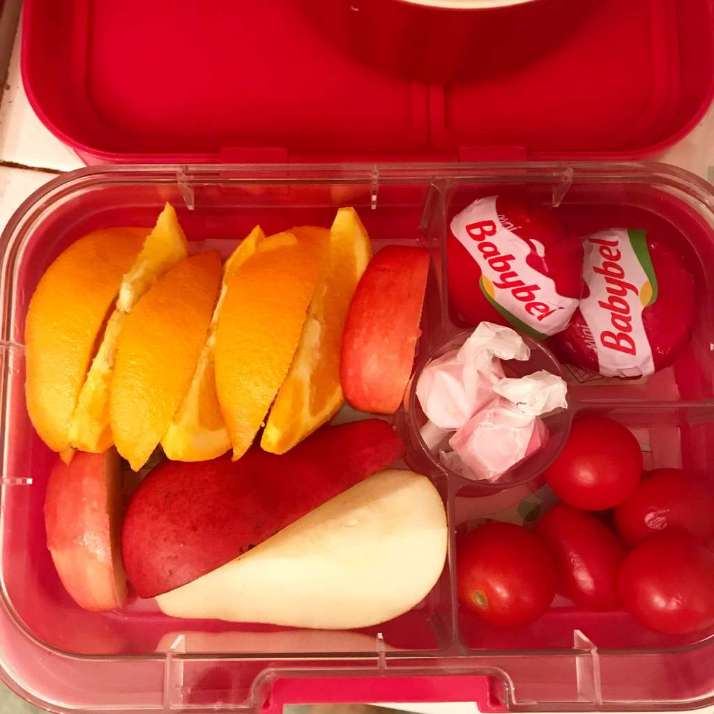 Example of school lunches with orange slices, pear slices, apple slices, mini cheeses, grape tomatoes, and two pieces of taffy.