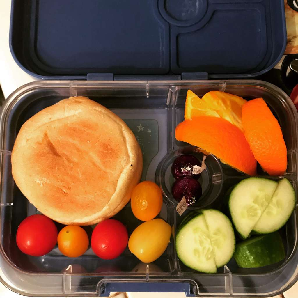 Child's bento box with sunflower seed butter and jam sandwich on an English muffin, a few mini tomatoes, cucumber slices, orange slices, and two dark chocolate Kisses.