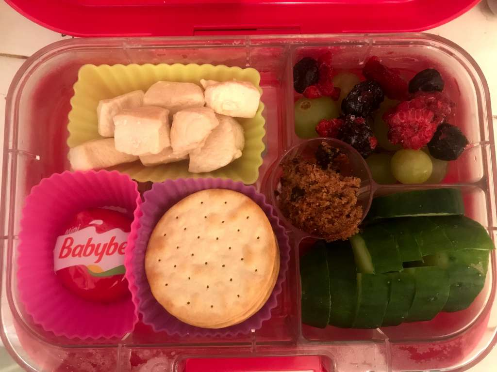 Child's bento box with leftover chicken, mini cheese, crackers, grapes and frozen mixed berries, cucumber slices, and a small piece of chocolate chip banana bread.