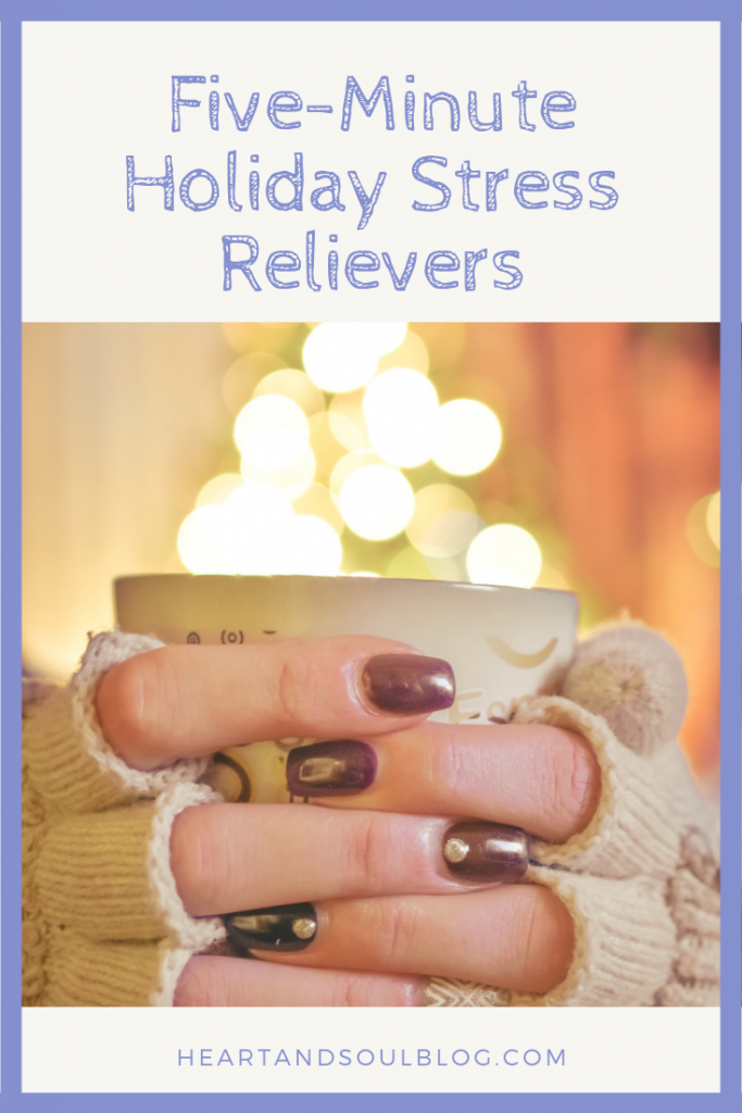 """White hands with painted fingernails and fingerless gloves hold a mug in front of holiday lights with the title, """"Five-Minute Holiday Stress Relievers"""""""