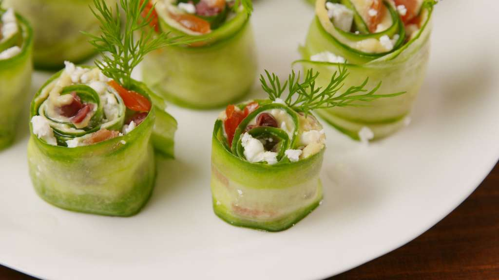 green sushi rolls on a white plate inside roll is white and red bits of tomato, cottage, cheese and ham