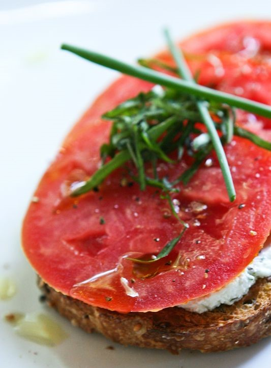 Slice of red tomato with sprigs of green parsley garnished on top. The tomato sits on top of a brown wheat bread and white cottage cheese.