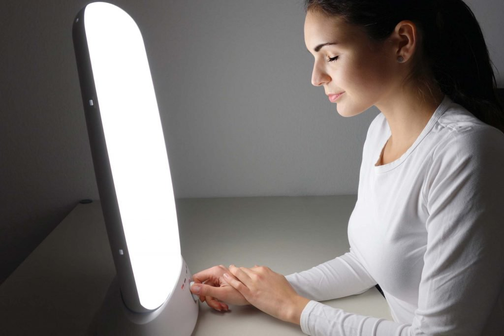 Woman with brown hair and white shirt sitting down and staring at a box emitting a white glow in a bare room