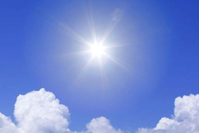 sun shining brightly in sky against blue background and white clouds below