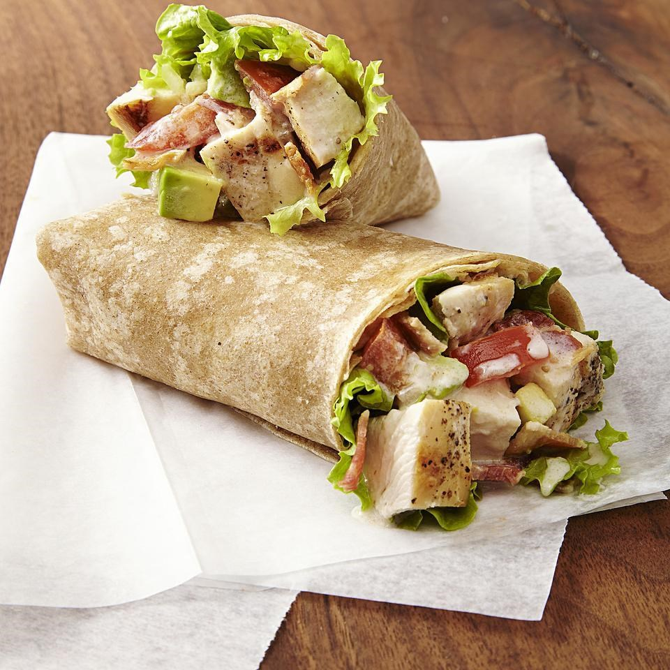Image of two brown chicken wraps filled with grilled chicken, lettuce, tomatoes resting on a brown table on top of a napkin