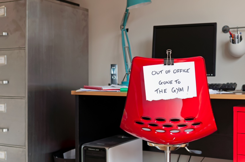 "Office setting with red chair, desk, computer, and filing cabinet. White note taped to red chair that reads in black ink ""out of office - gone to the gym"""