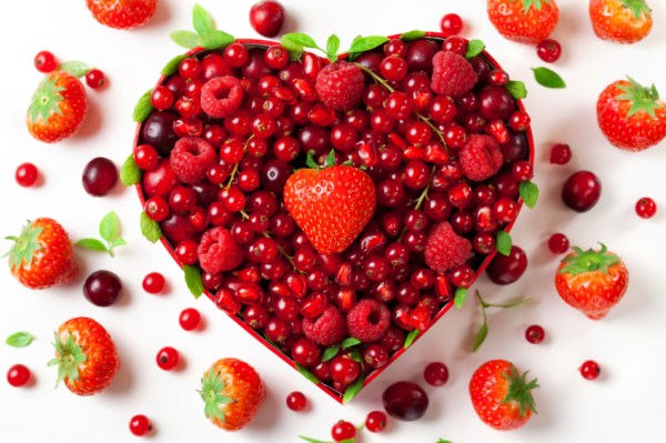 heart made of cherries and berries with a strawberry in the middle. White background with random berries floating