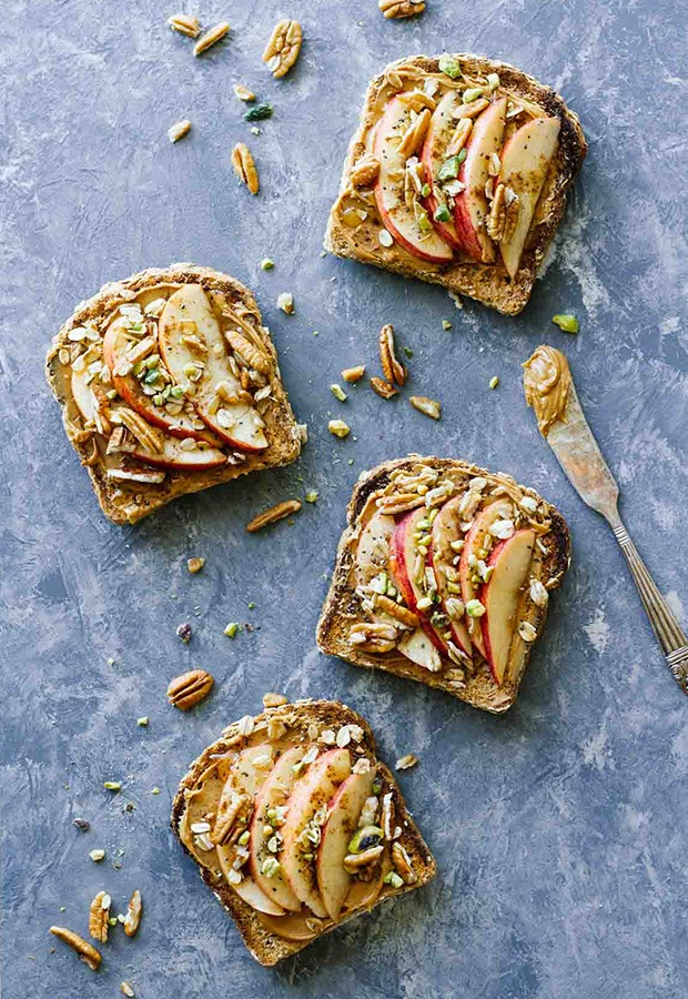 Open faced toast with apple slices and peanut butter next to toast is knife with peanut butter