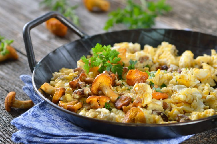 blue cloth with pan on top filled with scrambled eggs, mushrooms, and cheese plus green garnish