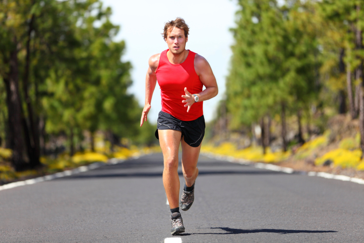 man running on road to camera wearing red shirt and black shorts