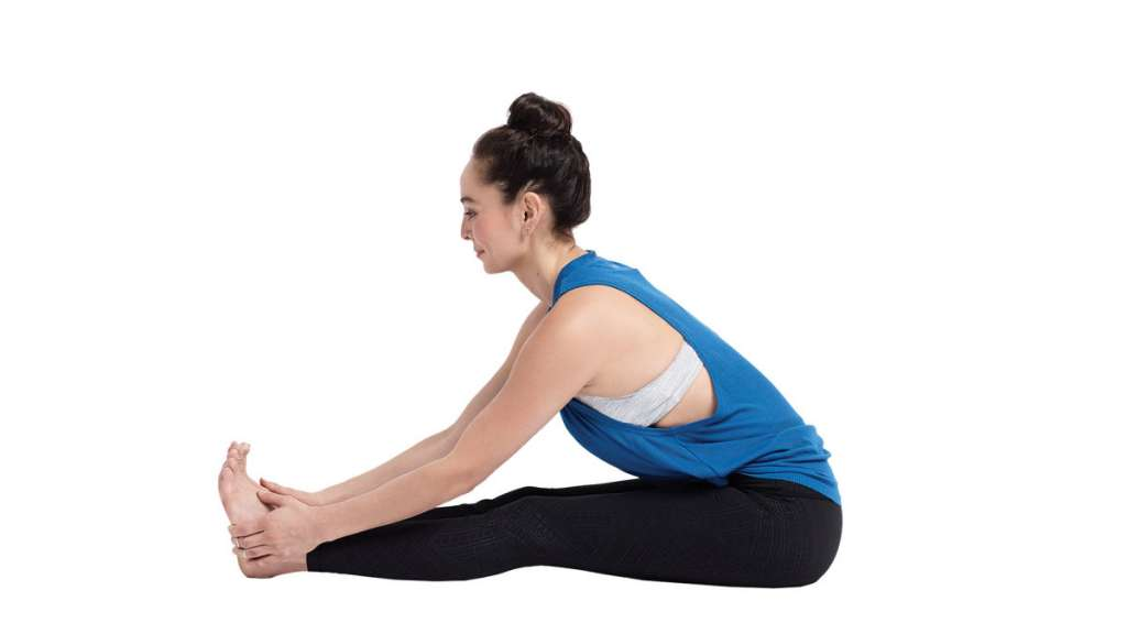 Woman in black pants and blue shirt sitting on floor stretching to her toes with white background