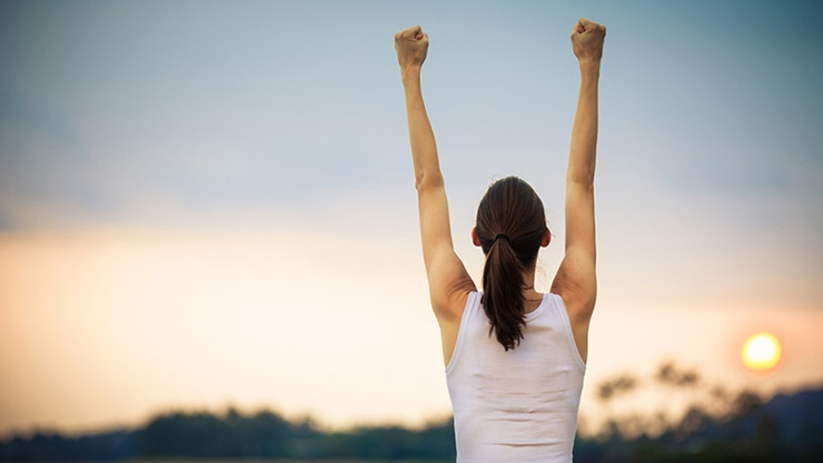 woman in white tank top raising her fists in the air the background is a sunset