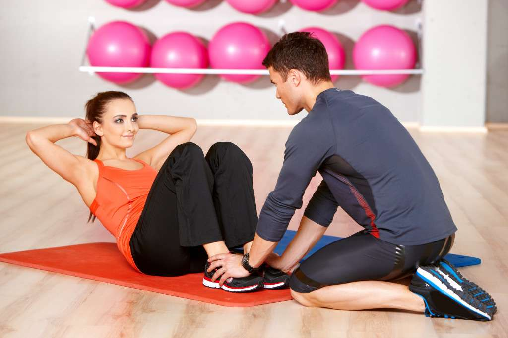 A woman in an orange tank top and black pants doing sit ups and a man in a gray outfit helping her with reps in a gym with pink workout balls in the background
