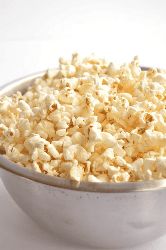 popcorn in a white bowl in front of white background