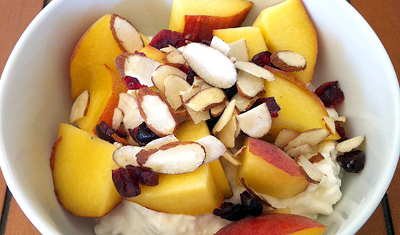 white bowl filled with cottage cheese, sliced peaches, and almonds