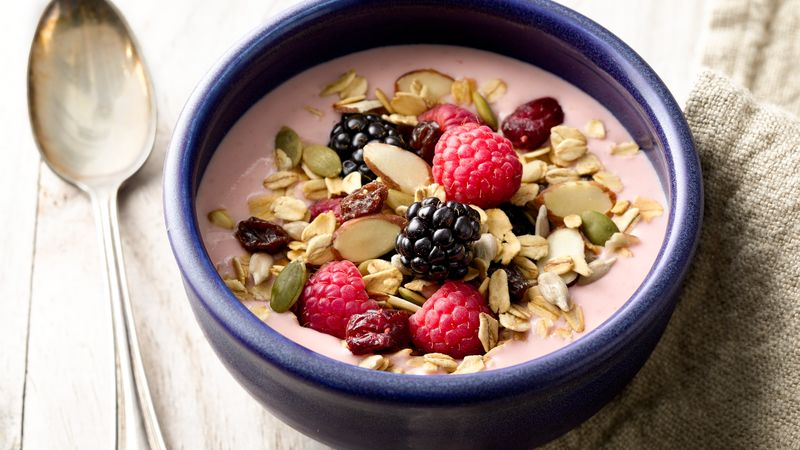 silver spoon and purple bowl filled with pink greek yogurt, mixed berries, and oats