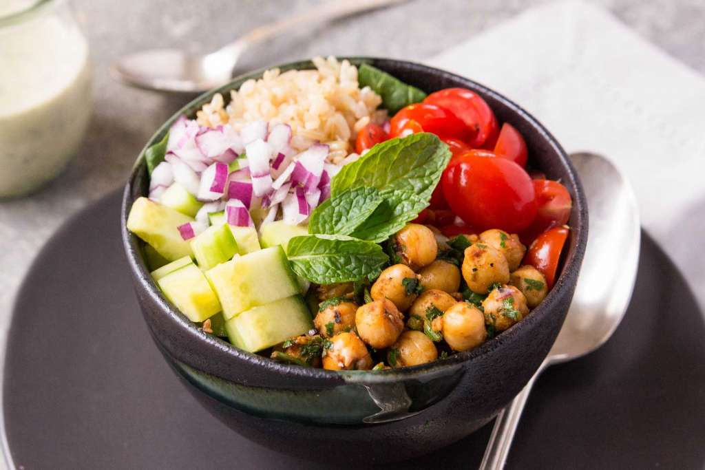 black bowl full of chickpeas, quinoa, sliced tomatoes, and salad
