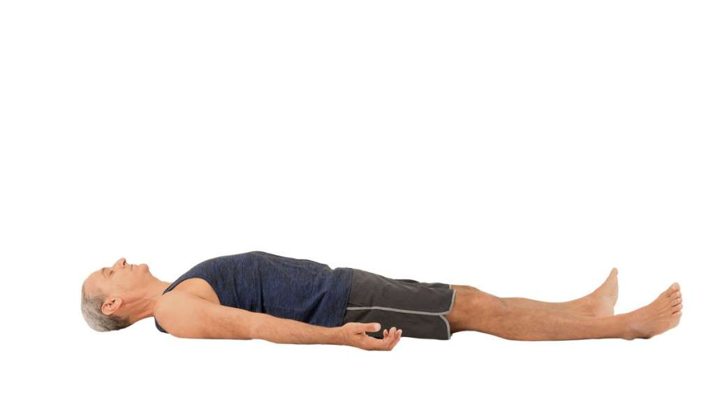 man laying down in yoga corpse pose