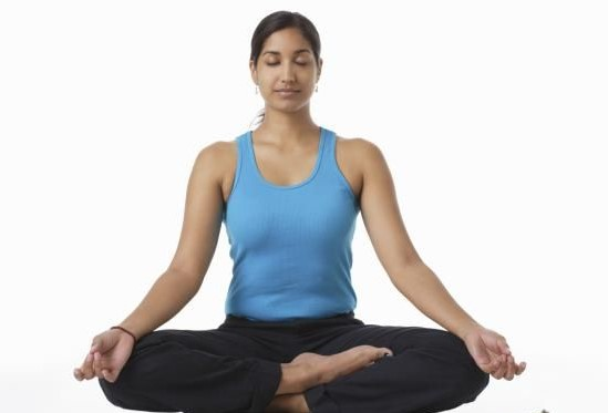 woman sitting indian style in yoga pose deep breathing