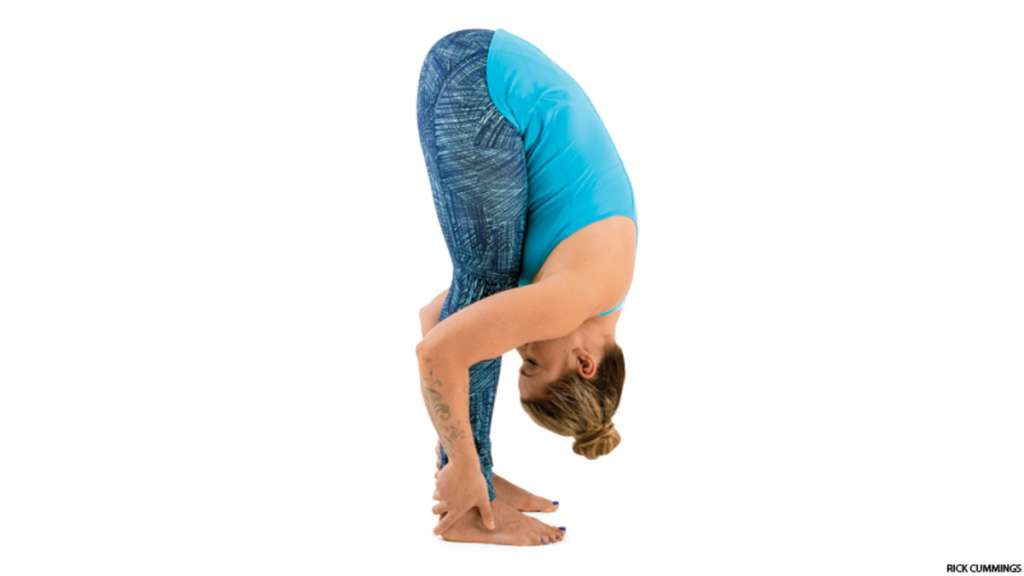 woman bending over and touching toes for yoga pose