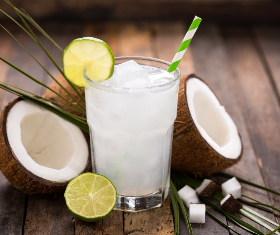 glass of coconut water with straw and lime wedge and cracked coconuts surrounding the glass