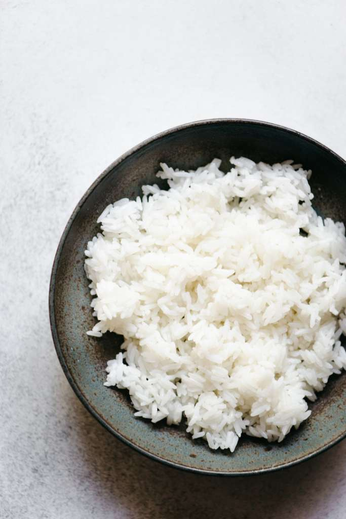 black bowl filled with white jasmin rice against white background