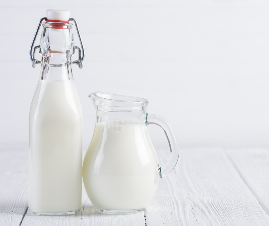 two clear glass jars of milk against white background