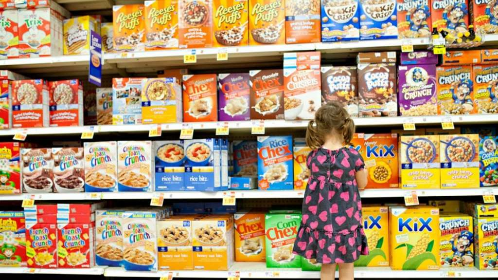 little girl looking at cereal aisle