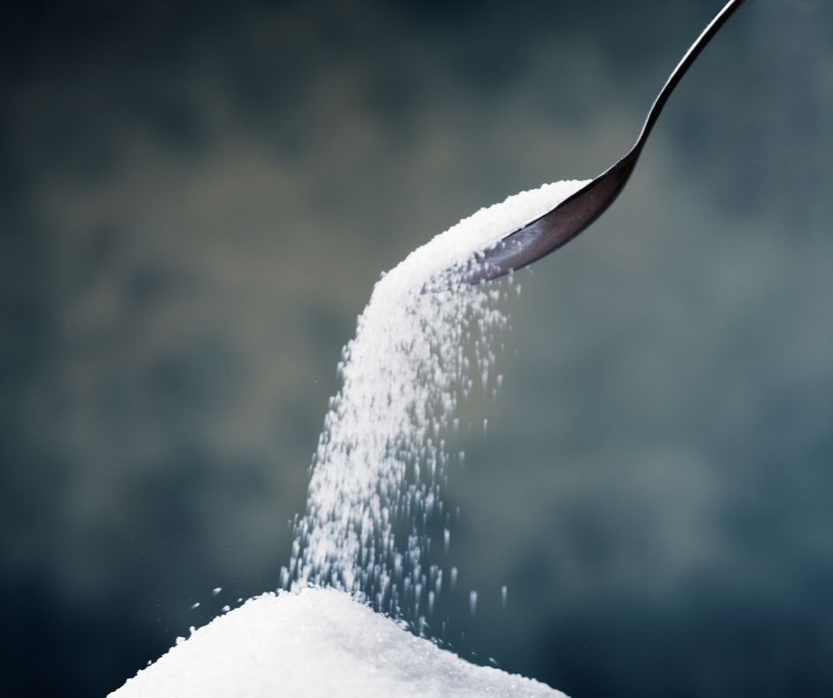 sugar from spoon falling into sugar pile