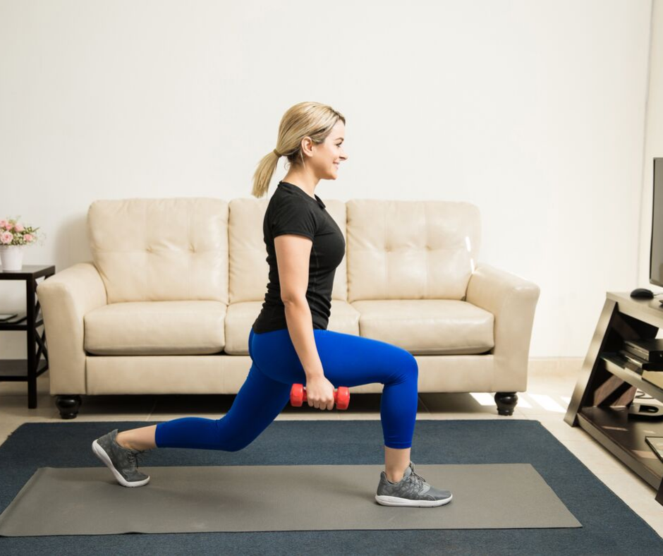 woman in living room next to couch doing lunges and holding weights