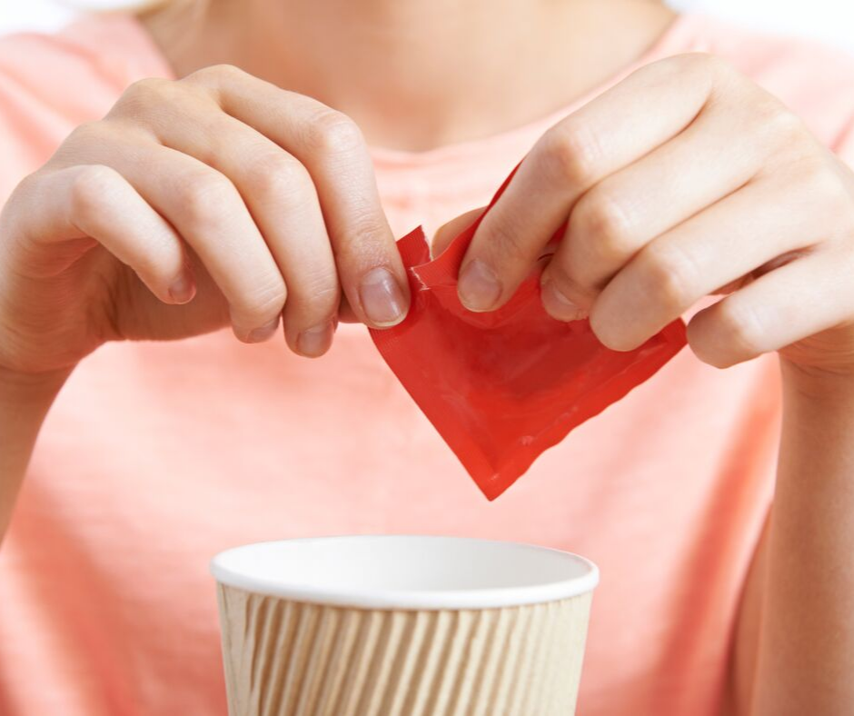 woman ripping red sugar packet into her white mug