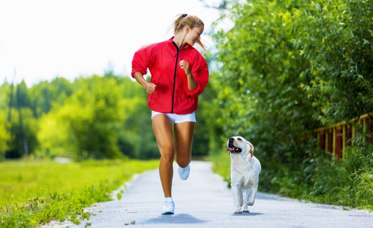 woman running next to dog