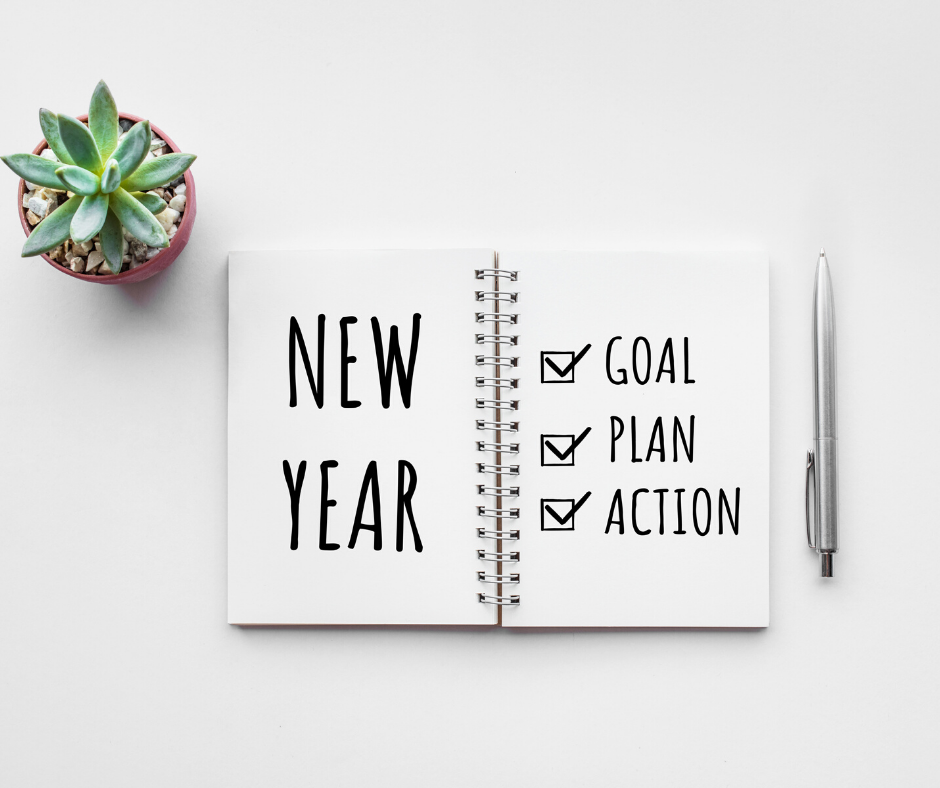 journal next to plant that says new year new goals