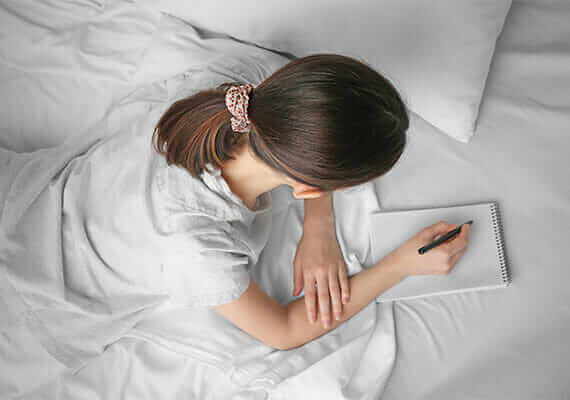 woman in bed writing in journal