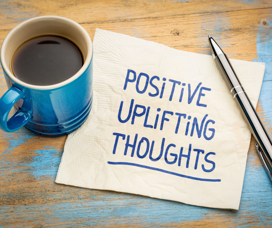 """coffee on table next to pen and napkin reads """"Positive uplifting thoughts"""""""