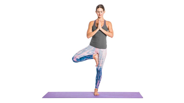 woman standing on yoga mat in a tree pose