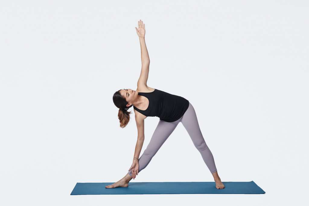 woman practicing triangle pose on a yoga mat