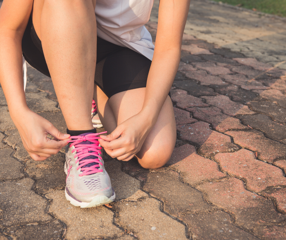 Woman tying shoelaces about to use different running apps